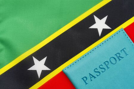 A passport stands against the flag of Saint Kitts and Nevis. The concept of travel and tourism. 写真素材