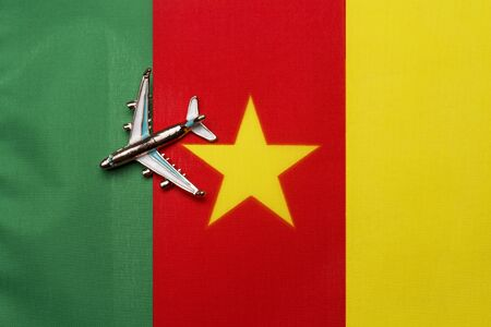 Plane over the flag of Cameroon, the concept of travel and tourism. Toy plane on a flag in the background. Stock Photo