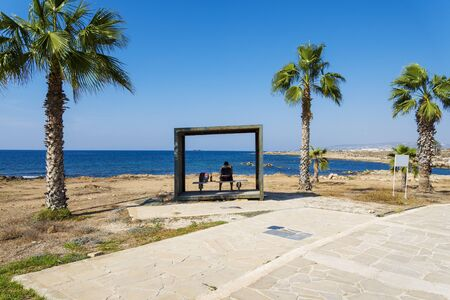 A man sitting on a bench overlooking the sea island of Cyprus. The concept of recreation and entertainment. Stock Photo