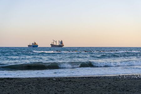 Cargo ships on the horizon of the Mediterranean sea. Ships near the coast of Cyprus, Limassol.