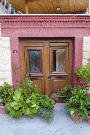 Drewniane drzwi wejściowe i doniczki z kwiatami. Piękne tylne drzwi na Cyprze.
