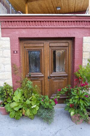 Puerta de entrada de madera y macetas de flores. Hermosa puerta trasera en Chipre.
