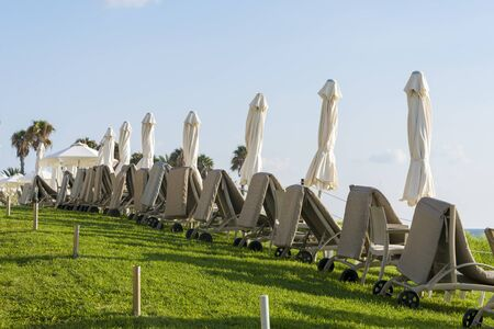Empty folding sun loungers on the grass in low season. The concept of recreation and entertainment. Stock Photo