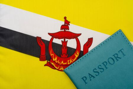 On the background of the flag of Brunei Darussalam is a passport. The concept of travel and tourism.