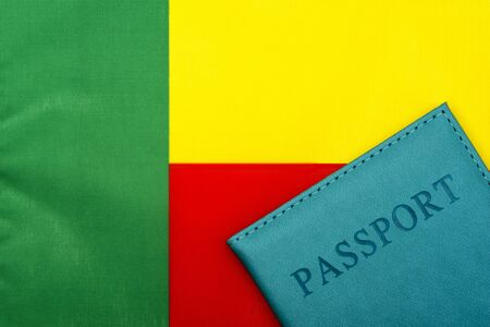 On the background of the flag of Benin is a passport. The concept of travel and tourism.