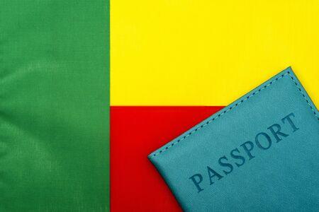 在贝宁的旗帜的背景上是护照。旅行和旅游的概念。