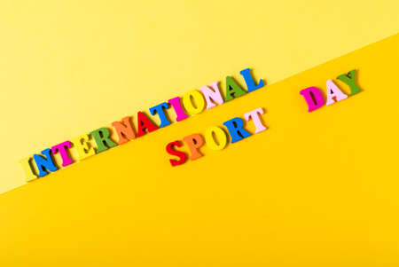 Wooden letters International Sports Day on a yellow background. The concept of the development of sports in the world, the holiday on April 6.