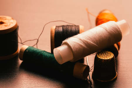 many Vintage spools of thread and a thimble on a wooden background Stock Photo
