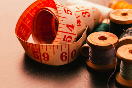 Vintage spools of thread thimble and measuring tape on a wooden background