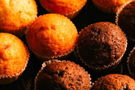 Chocolate muffins with nuts on dark  background, selective focus