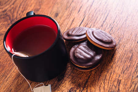 lot of chocolate chip cookies and a cup of tea on a wooden background Stock Photo