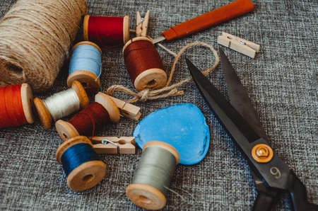 retro sewing tools: old scissors, bobbins of thread on gray fabric. Tailor's desk. manufacture of textiles or fine fabrics.