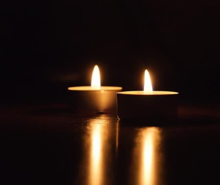 Closeup of burning candles isolated in front of black background photo