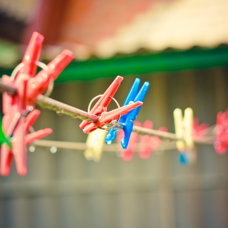 Colorful clothes pegs hanging in the line wire