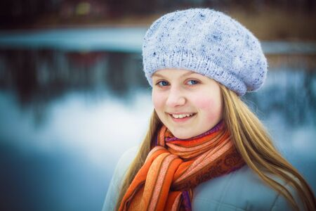 teen girl wearing white beret and orange scarf in windy day photo