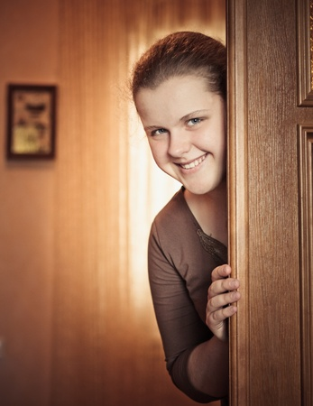 Beautiful Girl Peeking Behind The Door photo