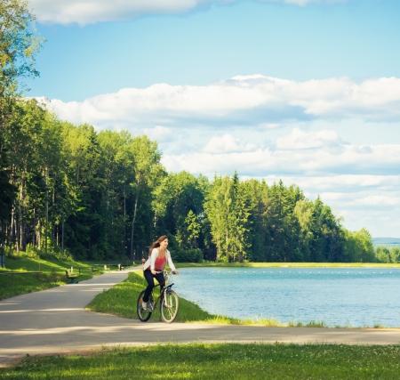Girl On A Bicycle Near Beautiful Lake Stock Photo - 17337446