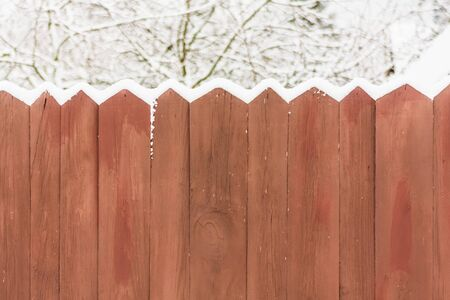 Old wooden fence in a snow photo