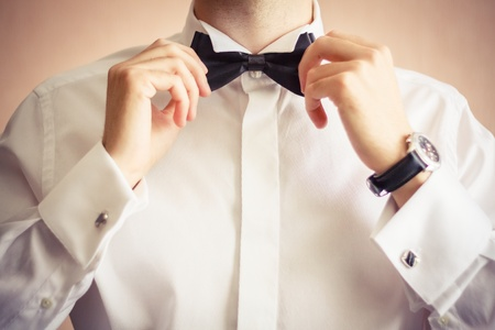 Closeup of business man adjusting neck bow over brown background Stock Photo - 18097695