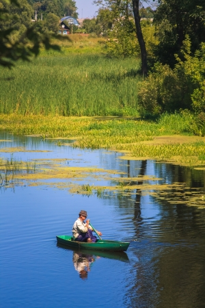 Old man fishing out of a row boat Stock Photo - 18522313