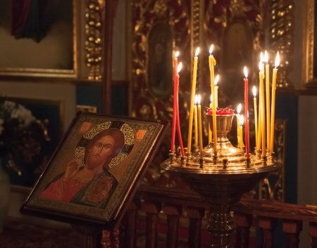 GOMEL - MAY 4: Interior of Belarusian orthodox church in Easte. Candles under the ancient icon framed with the gold on May 4, 2013 in Gomel, Belarus