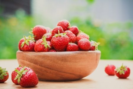 Old wooden bowl filled with succulent juicy fresh ripe red strawberries on an old wooden textured table top Stock Photo