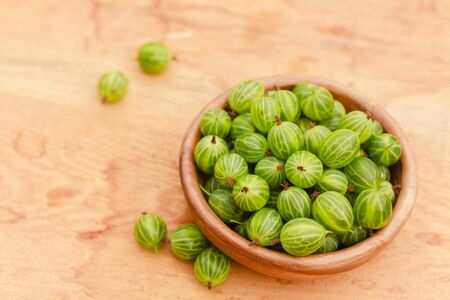 Old Wooden Bowl Filled With Succulent Juicy Fresh Ripe Green Gooseberries On An Old Wooden Table Top. photo