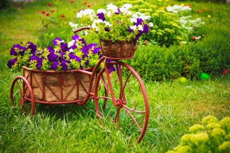 오래된 자전거의 장식 모델은 꽃 바구니와 함께 갖추고 있습니다.