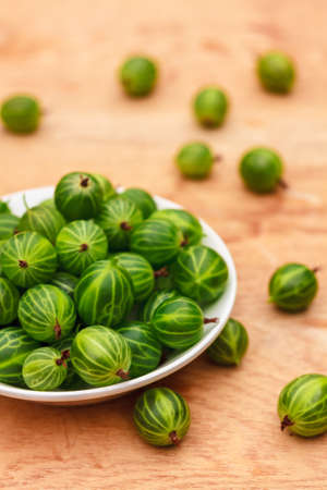 White Dish Filled With Succulent Juicy Fresh Ripe Green Gooseberries On An Old Wooden Table Top. Stock Photo