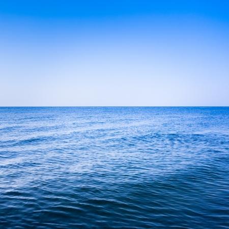 Kalme zee oceaan en de blauwe heldere hemel Stockfoto