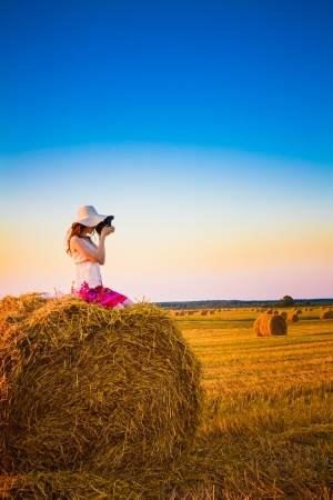 Beautiful young girl woman in dress sitting on haystack and making photos with vintage film camera in sunny day in field, meadow photo