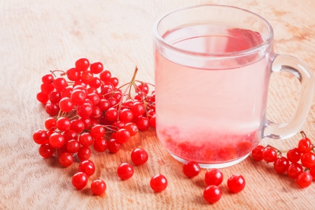 Tea with red viburnum on wooden table background