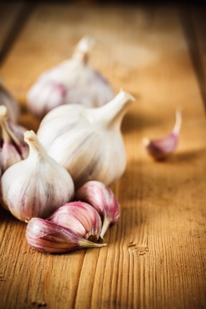 White raw garlic on wooden plank desk background. Organic garlic whole and cloves Stok Fotoğraf