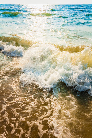 Soft sea ocean waves wash over sand background. Sunset, sunrise