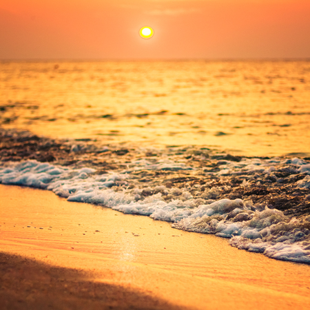 Soft sea ocean waves wash over golden sand background. Sunset, sunrise, sun. Close focus waves Stock Photo