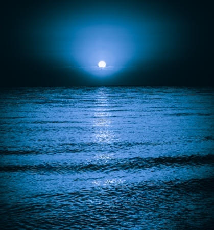 Moon reflecting in a lake sea ocean waves. Moonlight night background Standard-Bild