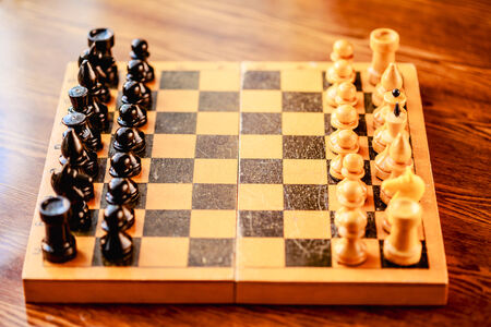 Chess standing on ancient wooden chessboard Stock Photo