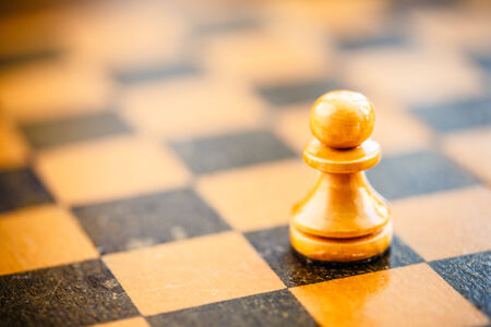 Chess white pawn standing on old vintage chessboard photo