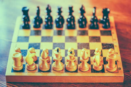 Chess standing on ancient wooden chessboard photo