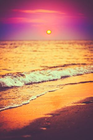 purple sunset: Sea Ocean Waves Wash Over Golden Sand Background. Sunset, Sunrise, Sun. Close Focus Waves
