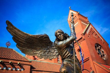 Statue of Archangel Michael with outstretched wings, thrusting a spear into a dragon before the Catholic Church of St. Simon and St. Helena. The sculpture symbolizes the victory of the heavenly host over the forces of darkness. Red Church is a Roman Catho Stock Photo