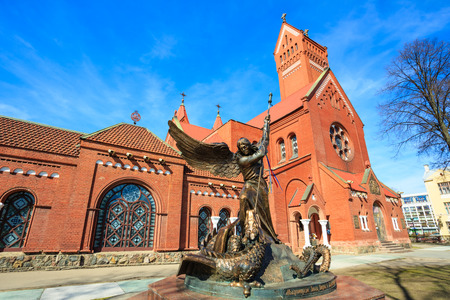 helena: Statue of Archangel Michael with outstretched wings, thrusting a spear into a dragon before the Catholic Church of St. Simon and St. Helena. The sculpture symbolizes the victory of the heavenly host over the forces of darkness. Red Church is a Roman Catho Stock Photo