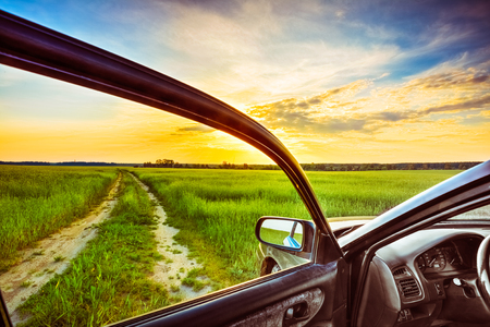 Dirty rural road in field, meadow, countryside. View from car window. Freedom and dream concept photo