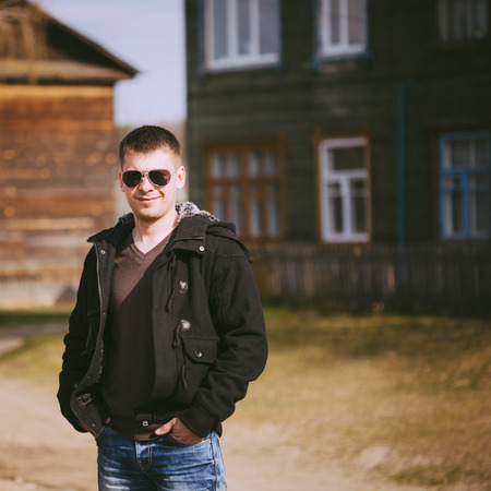 Young handsome man staying near old wooden house in autumn day, relaxing,  thinking, smiling. Casual style - jeans, jacket, sunglasses Stock Photo