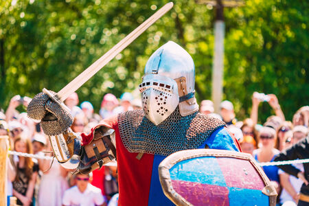 Historical Restoration Of Knightly Fights. Summer Time. Knight In A Fight With Sword photo