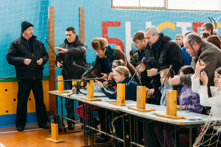 school sports: GOMEL, BELARUS - JANUARY 1, 2011: Unrecognizable Belarusian secondary school pupils girls shooting an air rifle at a school sports competition Ski sniper among school children Editorial