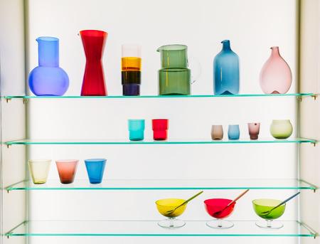 material de vidrio: Una variedad de diferentes tama�os y formas de colorido cristaler�a En Estantes. Floreros, jarras, jarros, vasos sobre fondo blanco.