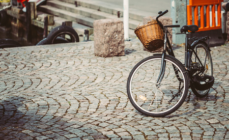 bike parking: Vintage Bicycle With Basket Parked On Sidewalk. Bike Parking In Big City. Toned Instant Photo