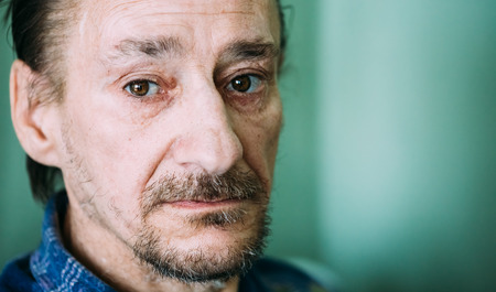 수염은 녹색 벽 배경에 카메라를 찾고 심각한 슬픈 옛 성인 표현 남자의 초상화 스톡 콘텐츠