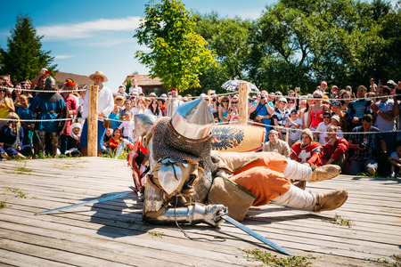 MINSK, BELARUS - JULY 19, 2014 Historical restoration of knightly fights on festival of medieval culture. Defeated In Battle Knight Tries To Get Up From The Floor